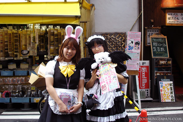 Cute Japanese women / girls in front of a maid cafe in Akihabara.