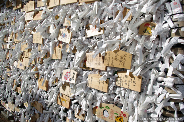 Omikuji and ema (wooden wishing plaques) next to each other in Onomichi